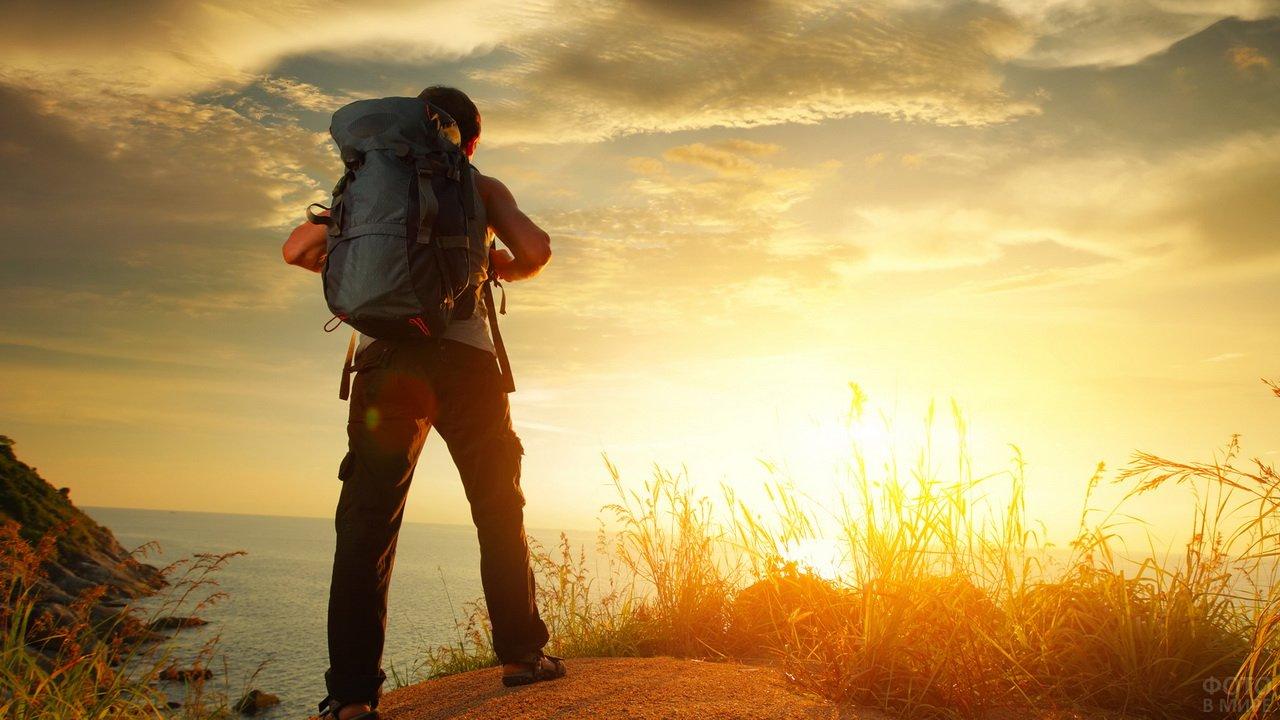 Человек с рюкзаком на фоне заката
