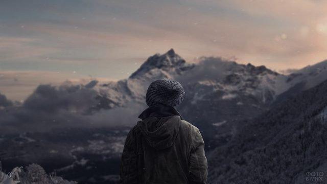 Человек в вязаной шапке на фоне гор