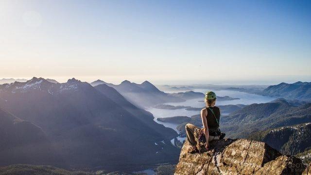 Девушка альпинист на вершине горы