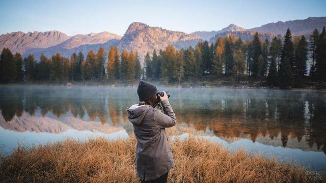 Девушка фотограф снимает природу в горах
