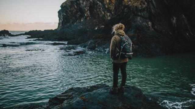 Девушка с небольшим рюкзаком на морском берегу