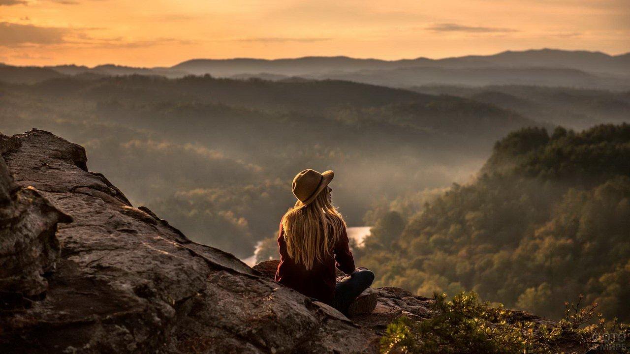 Девушка сибит на фоне гор