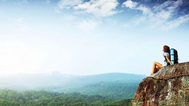 Девушка турист на скале над долиной