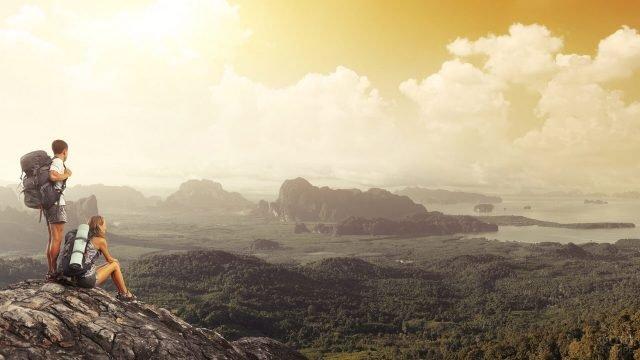 Двое туристов с рюкзаками на вершине горы смотрят в долину