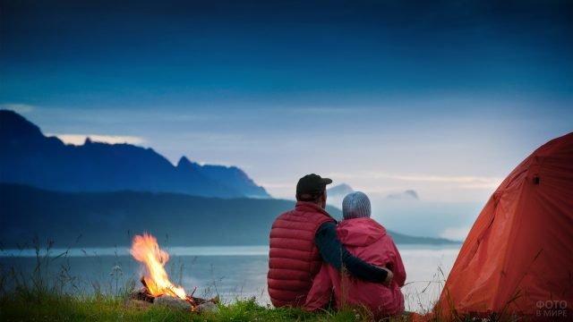Двое туристов у палатки и костра сидят обнявшись