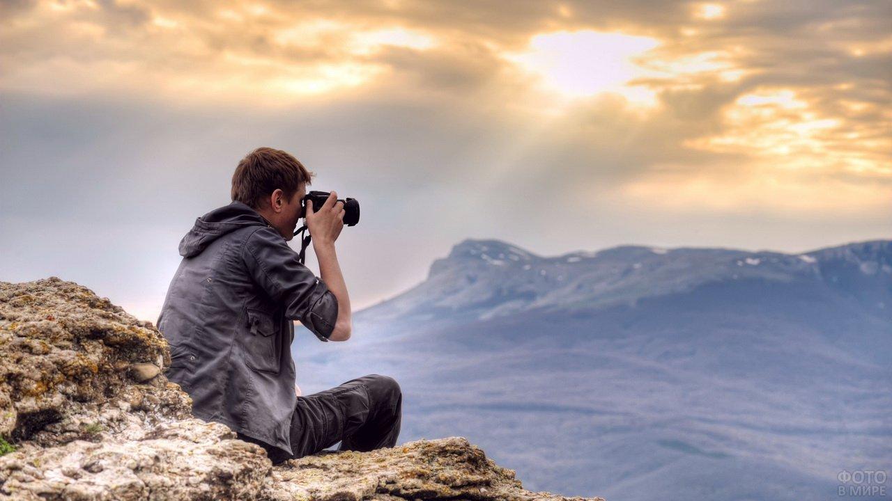 Фотограф-путешественник снимает горы на фотоаппарат