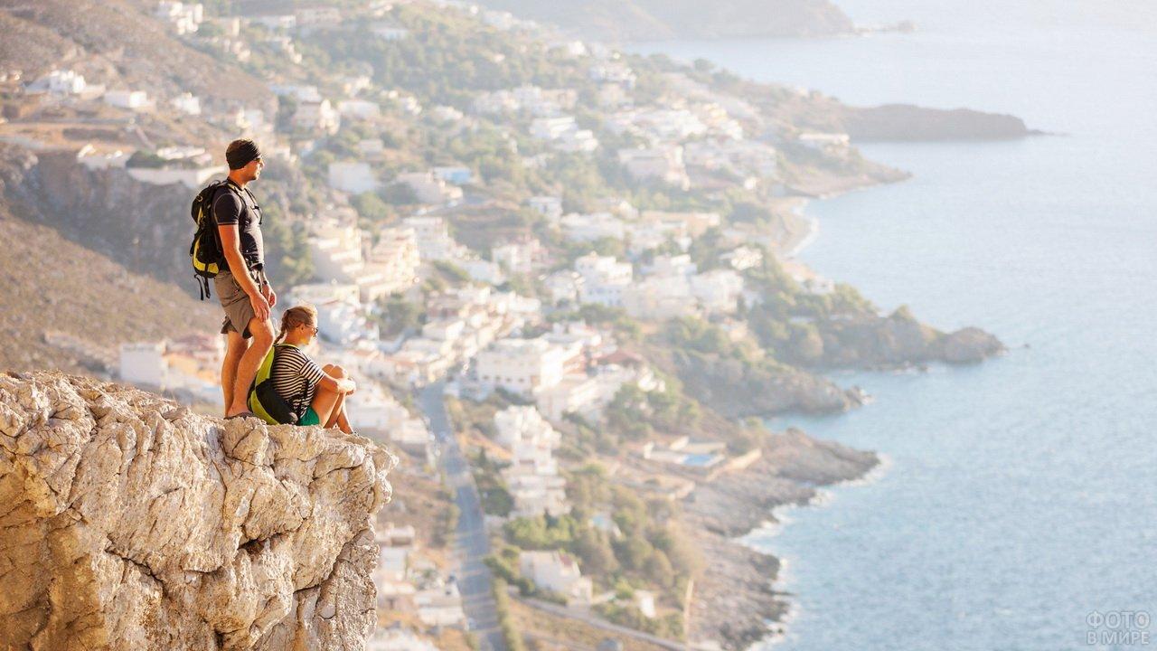 Мужчина и девушка в горах над городом и морем