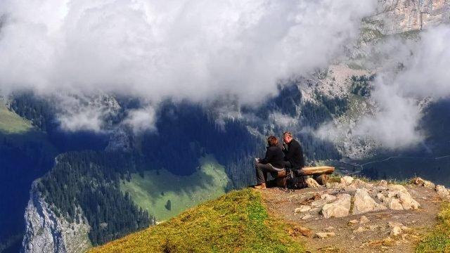 Мужчина и женщина сидят на лавке на фоне гор
