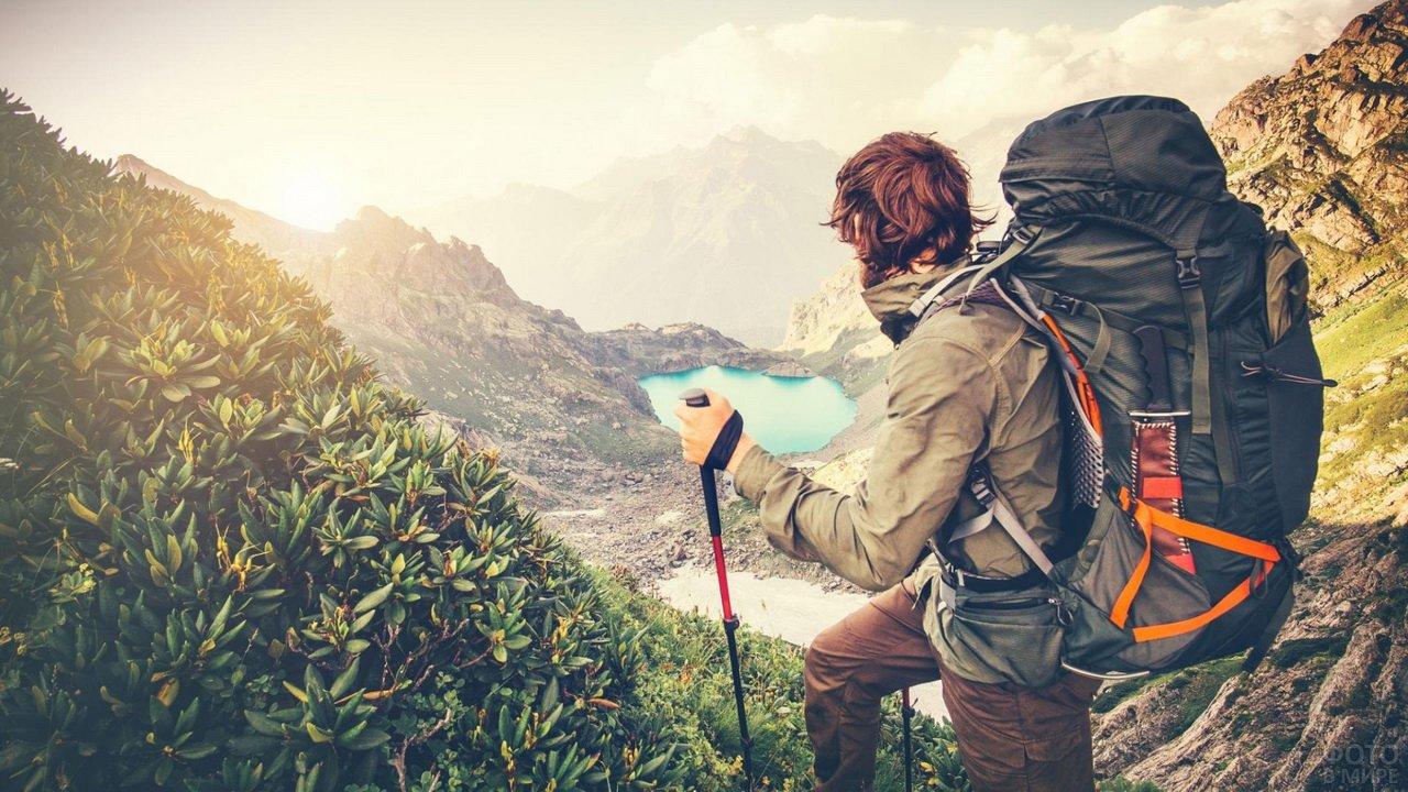 Мужчина с рюкзаком и палками для ходьбы в горах