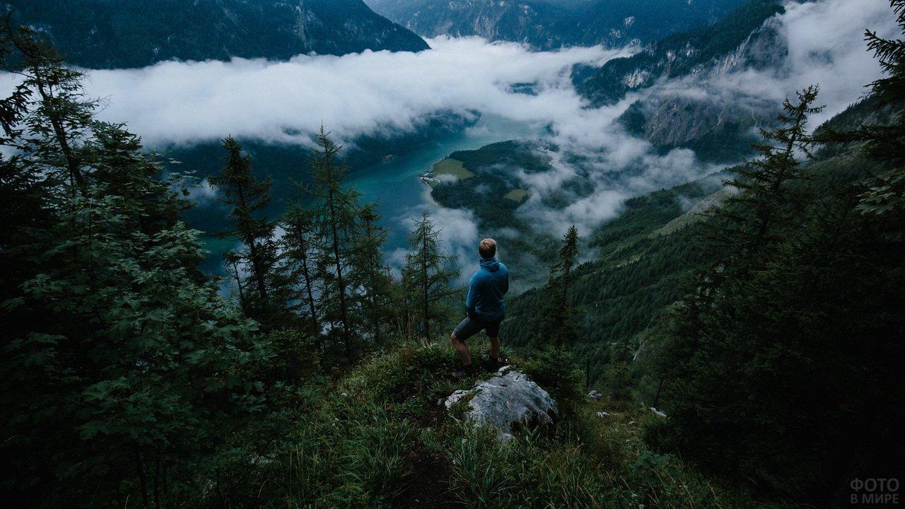 Мужчина высоко в горах над долиной с озером