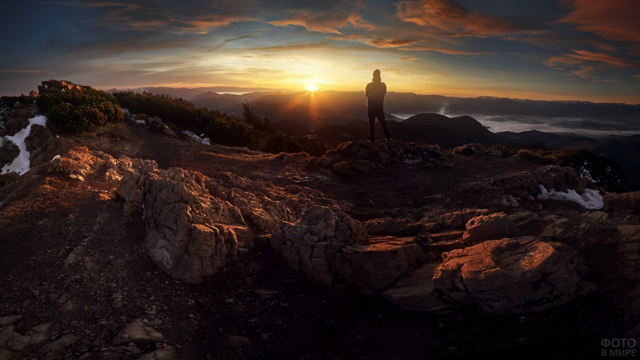 Путешественник на вершине горы на закате