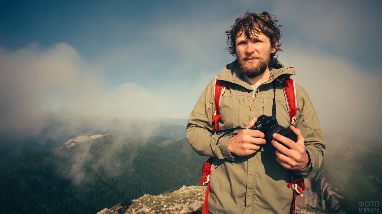 Путешественник с фотоаппаратом в руках на фоне гор