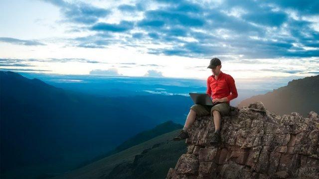Путешественник с ноутбуком на коленях на обрыве в горах