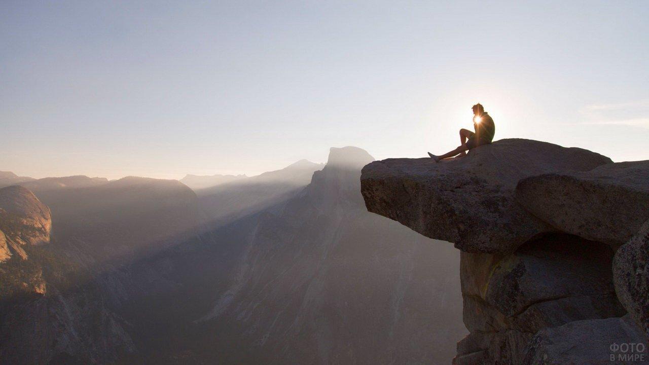 Путешественник сидит на огромном камне над обрывом в горах