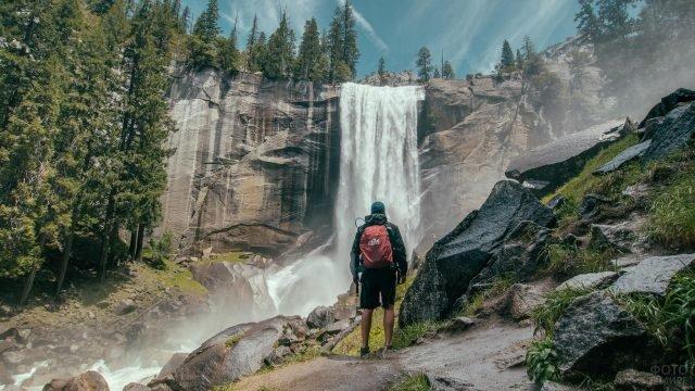 Путешественник со спины на фоне водопада