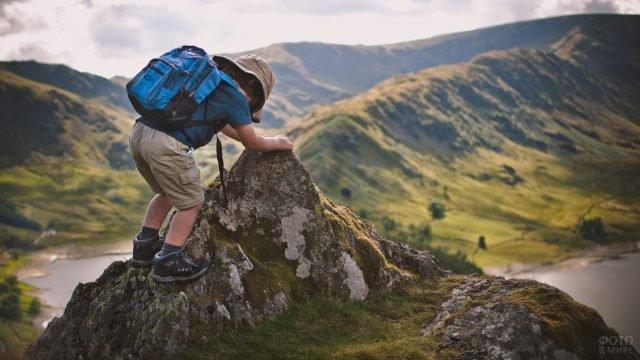 Ребёнок маленький турист залазит на вершину