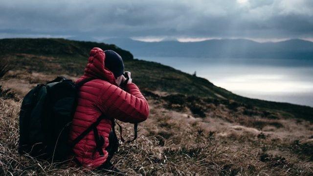 Турист фотографирует пейзаж с озером