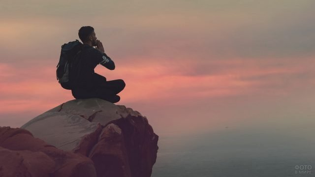 Турист на камне над обрывом в молитвенной позе