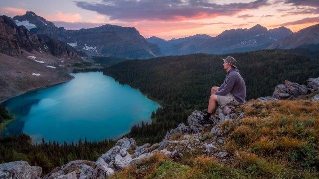Турист на камнях над горным озером
