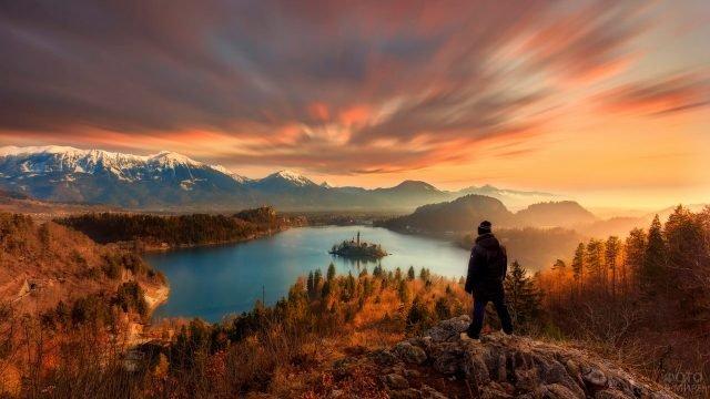 Турист на возвышенности над озером с островком посередине