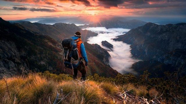 Турист с большим рюкзаком в горах на закате