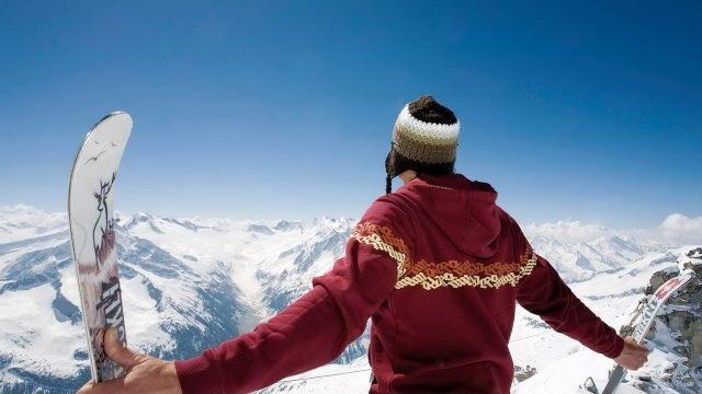 Турист с горными лыжами на вершине