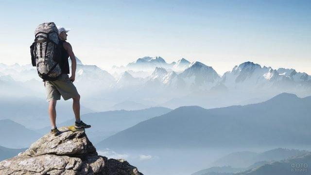 Турист с рюкзаком на возвышенности на фоне гор