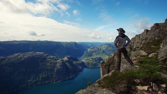 Турист в горах над обрывом смотрит на озеро внизу