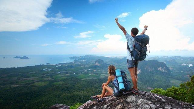 Туристы парень с девушкой на возвышенности над долиной и далёким морем