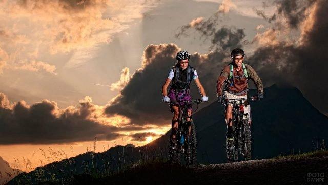 Велотуристы на фоне гор и чернеющего неба
