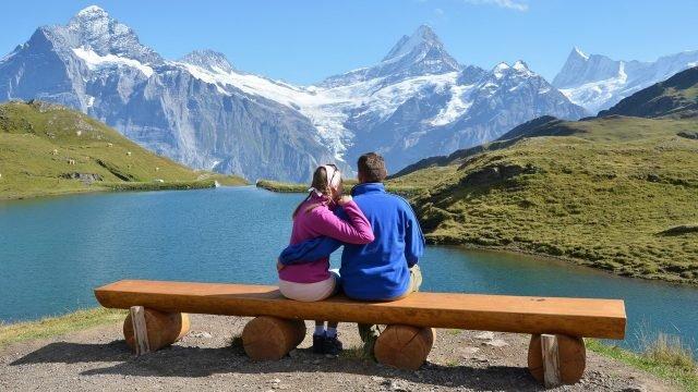 Влюблённая пара в горах на фоне высокогорного озера