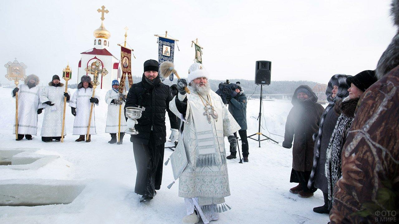 Батюшка окрапляет прихожан на празднике Крещения