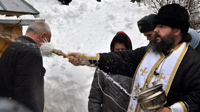 Батюшка освящает прихожан на праздничной службе у крещенских купелей в Подмосковье