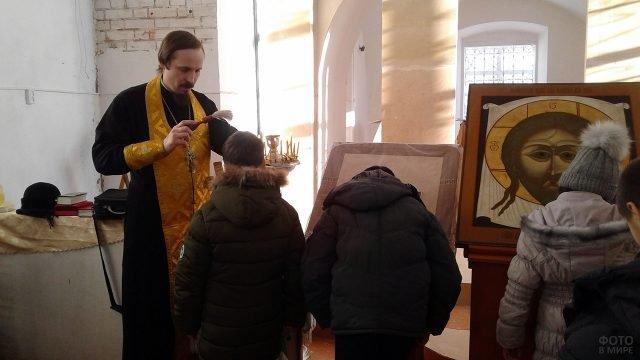 Дети благославляемые батюшкой в церки на празднике Крещения Господня
