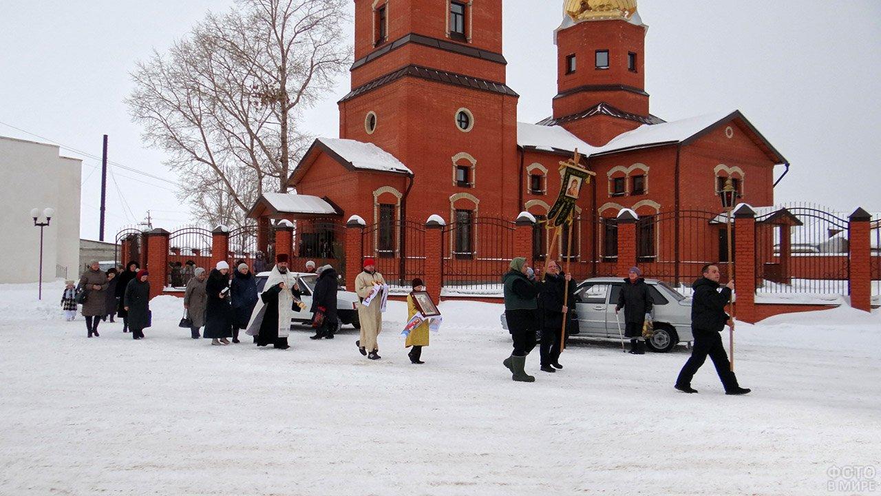 Крестный ход выходит из ворот церкви на Крещение в городке Саратовской области