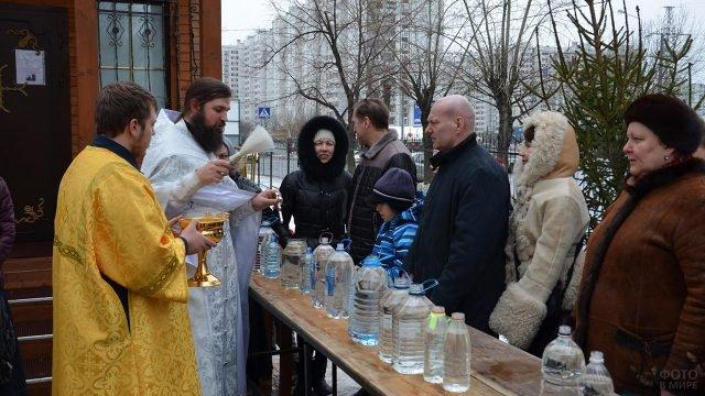 Освящение воды и прихожан у стен московского храма в день Крещения Господня