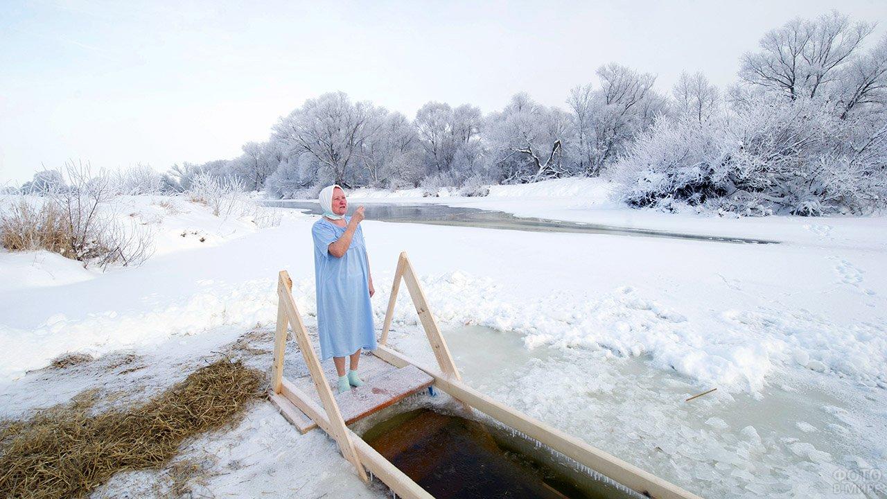 Пенсионерка у живописной деревенской купели на празднике Богоявления
