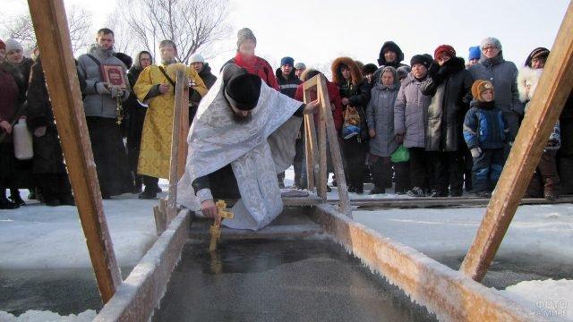 Православные и батюшка на обряде Водосвятия у проруби в день Богоявления