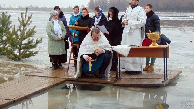 Батюшка в окружении церковного хора во время освящения проруби на Крещение