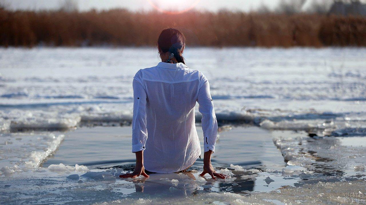 Девушка в белой одежде окунается в крещенскую прорубь
