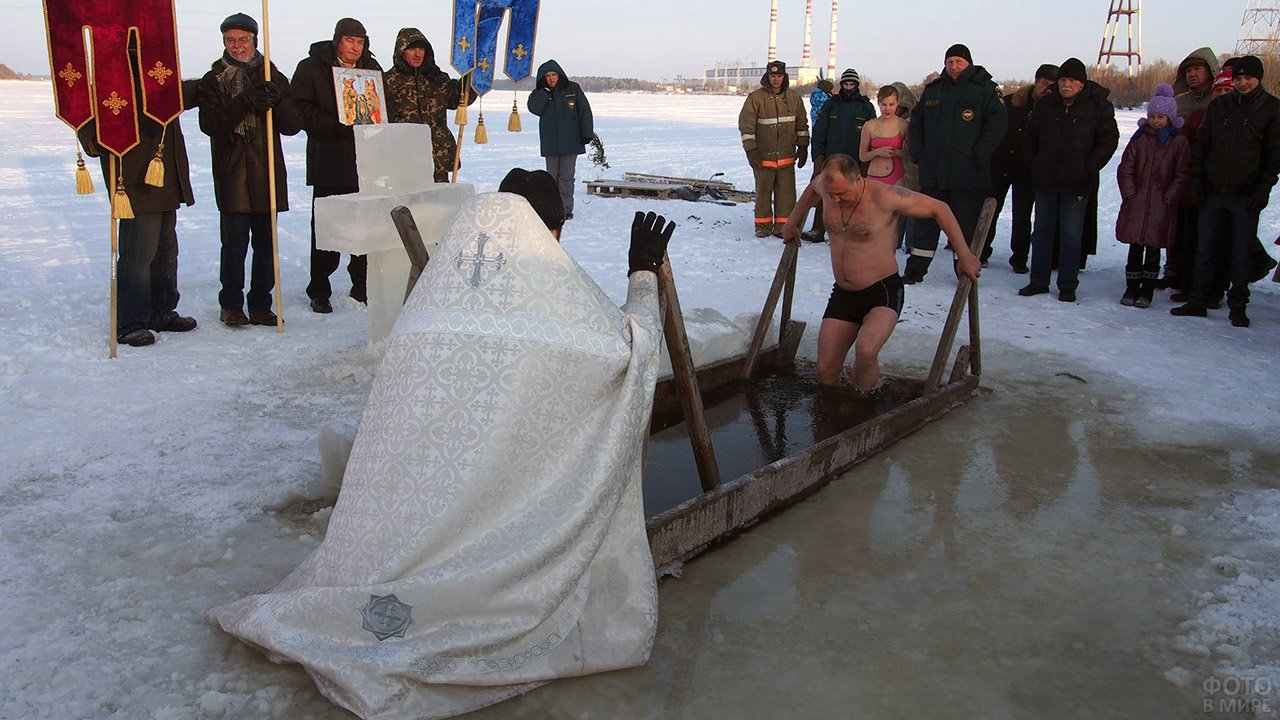 Мужчина благославляемый батюшкой окунается в прорубь на Крещении в Тверской области