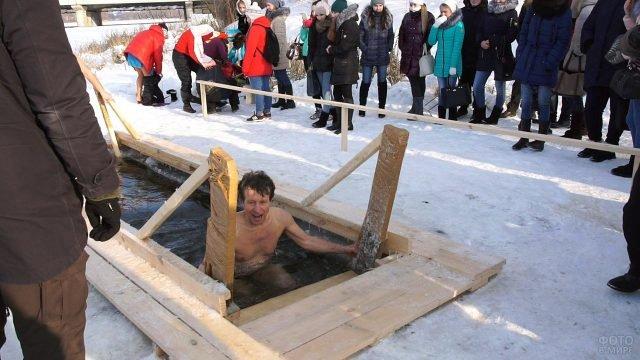 Мужчина вылезает из проруби на празднике Крещения в Ульяновске