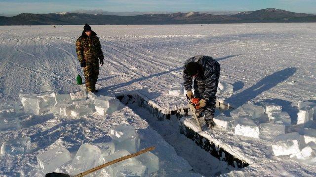 Мужчины вырубают крестообразную крещенскую прорубь на реке в Челябинской области