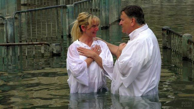 Паломники в белых одеждах в воде реки Иордан на Крещение Господне