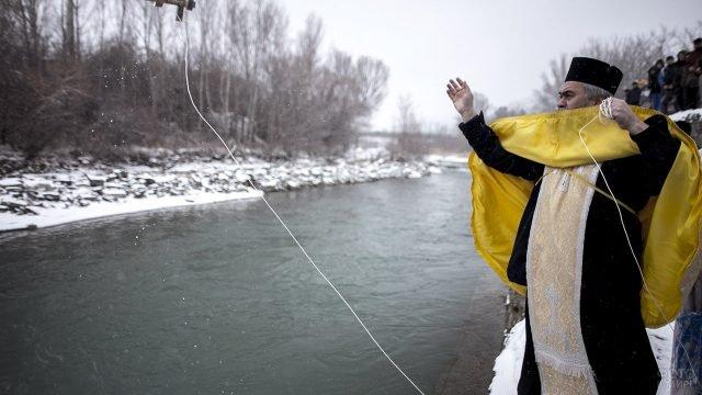 Православный батюшка у реки на празднике Крещения в Цхинвале