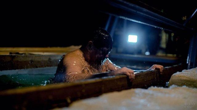 Вынырнувший из крещенской купели мужчина в свете вечернего фонаря