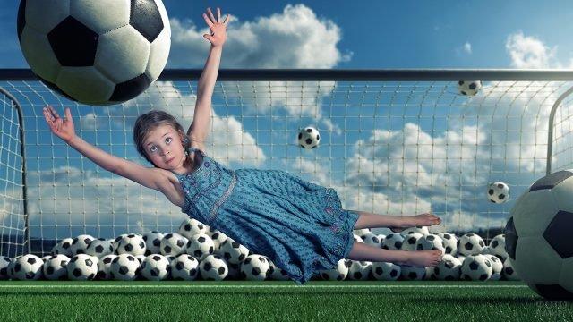 Девчушка в воротах ловит огромный футбольшый мяч