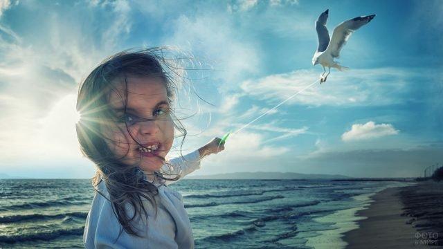 Девочка держит чайку на нитке