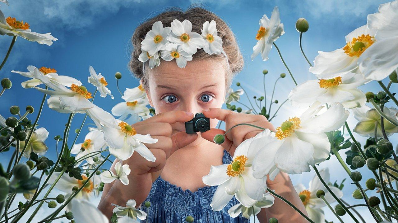 Девочка фотографирует цветы маленьким фотоаппаратом