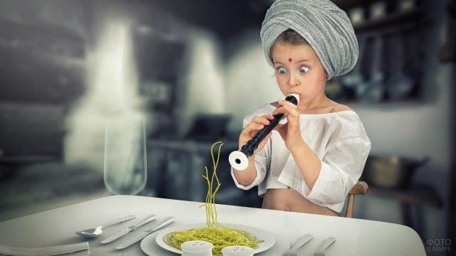 Девочка играет на дудочке, зачаровывая макароны в тарелке